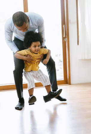 Happy African American father carry little son into the house while the child was playing on his father's shoes after work. Welcome back home daddy or family reunion concept. 免版税图像 - 159126283