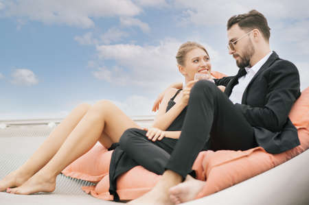 Romantic portrait of young caucasian couple toasting champagne on on luxury yacht in the sea. People celebrating wedding anniversary on boat trip. Love relationship and travel lifestyle concept.
