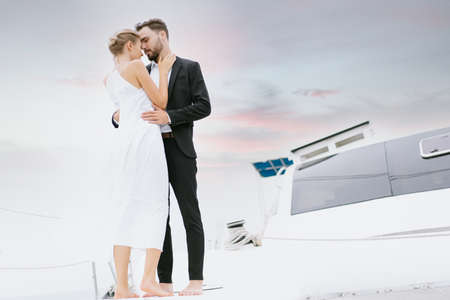 Portrait of young caucasian couple in love relaxing on luxury yacht in the sea. People celebrating wedding anniversary on boat trip. Love relationship and travel lifestyle concept. 版權商用圖片