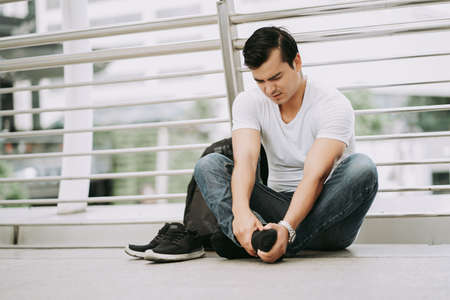 Traveling Asian male tourist sitting on street ground while suffering from casual shoes due to uncomfortable shoes, suffering from flat feet,painful foot,leg fatigue.Health problem and people concept. 免版税图像 - 159434344