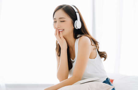 Portrait of young Asian woman smiling sitting in comfortable bed friendly listening to music in headphones enjoying singing song with eyes closed relaxing in cozy bedroom at home.Lazy day off concept.