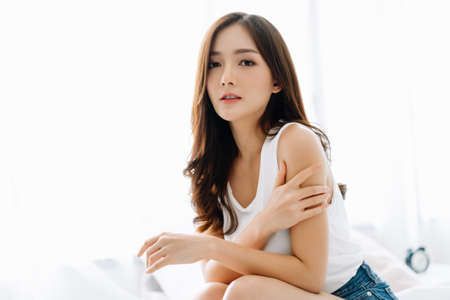 Portrait of beautiful Asian woman sitting on her bed applying body lotion on her attractive arm during her morning routine and looking at camera.Relax time,Skin Care,Beauty,Wellness and health Concept