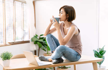 Portrait of beautiful young Asian woman relax sitting on office desk  enjoying her cup of coffee and thoughtfully looking out of window. Girl during work break. Enjoying time at home. 版權商用圖片