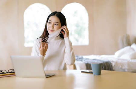Portrait of young woman Asian Freelancer in warm sweater working on laptop prepare to wear medical mask for protection flu and covid-19 at home.Work on winter holidays during self-isolation quarantine 免版税图像