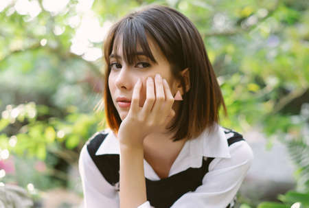 Closeup portrait of young Asian woman sitting on stone border and looking at camera in sunny park. Holiday activity and lifestyle concept. 免版税图像