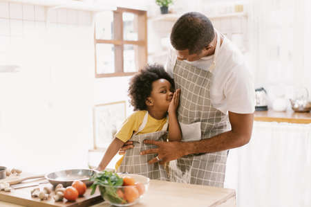 Happy African father and his son having fun and cooking in the kitchen at home. Cute little boy smiled and tried to kiss his father. Happy family activity together. 免版税图像