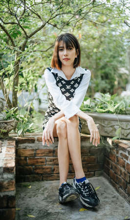 Portrait of young Asian woman sitting on stone border and looking at camera in sunny park. Holiday activity and lifestyle concept. 新闻类图片