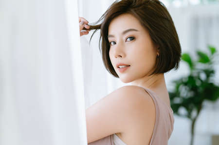 Beautiful young Asian woman standing near a window white curtains and turning to look and smile at camera. Pretty young girl posing and looking forward in bedroom at home. Lifestyle and Relax Concept.