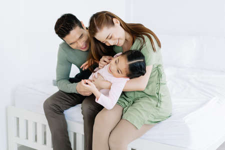 Happy loving Asian family. Portrait of beautiful mother and father are playing with daughter in the bedroom at home. Weekend activity happy family lifestyle concept.