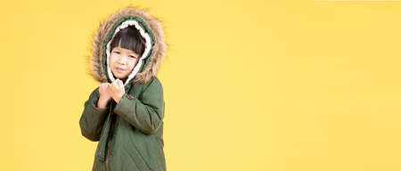 Adorable little Asian girl wearing a fur hooded winter green coat isolated on yellow background. Winter fashion, winter clothes. Wide crop, long horizontal banner, banner for website header Concept.