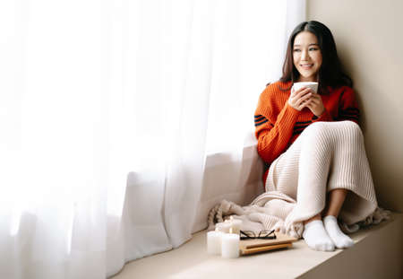 Young beautiful happy Asian woman wearing knitted warm sweater sitting home in the chair by the window with cup of hot drink at home.Cozy winter decorated with candles.Feeling comfortable at home. Imagens