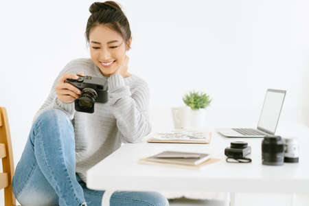 Portrait of young beautiful Asian female blogger photographer sitting at modern office while checking previews on camera.Happy Blogger and freelance work online marketing.Startup Small business owner.