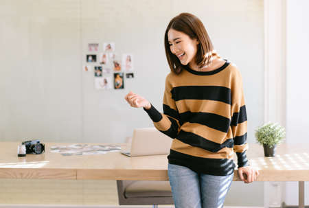 Smiling young beautiful Asian female blogger photographer standing in front of her desk at a bright home office studio. Happy Blogger and freelance work online marketing.Startup Small business owner. Imagens