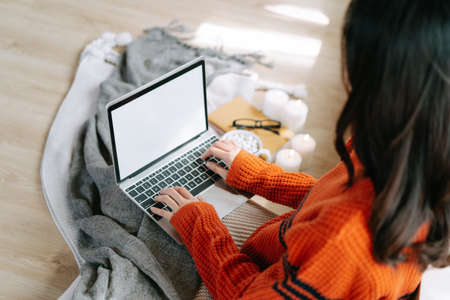 Top view, Young freelancer woman wearing knitted warm sweater sitting on ther floor and using laptop computer with cup of hot drink at home.Cozy winter decorated with candles.Work from home concept