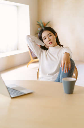 Bored young Asian woman wearing warm sweater clothes sitting with laptop at table home office has a problem with remote work. Feeling depression, exhausted, tired, lazy during working at home office.