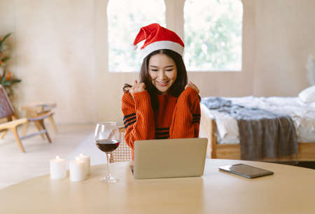 Smiling young Asian woman in warm knitted clothes and wearing santa hat.  She talking online on virtual video call party while celebrating Xmas holiday. Social distance, Christmas Celebrating Online.