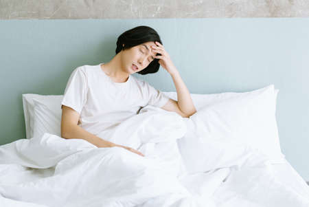 Young Asian man has suffering from strong headache or migraine while sitting in bed feeling tired, uncomfortable, dizzy after waking up in the morning,aching pain touching his head.Healthcare Concept