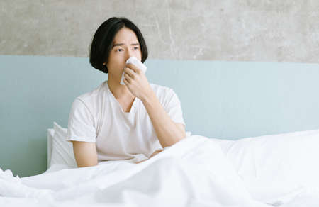 Young Asian man sitting on bed holding tissue handkerchief blowing running nose feels unwell unhealthy. Sick man having influenza symptoms coughing at hom. Seasonal allergy or cold fever flu concept.
