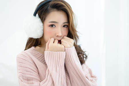 Adorable young Asian woman in warm pink sweater and cute fur earmuffs looking at camera while sitting on bed. Cute natural young female covering mouth. Concept woman lifestyle. Autumn, winter season.
