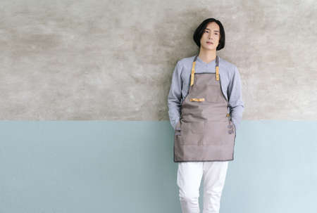Portrait of small business owner Asian male in vintage apron standing inside the his cafe and looking away. Startup of small business owner, SME concept.