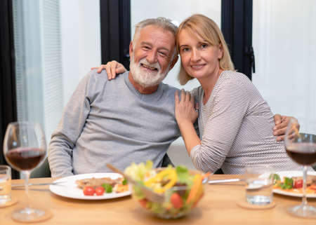 Happy senior couple having fun in living room playing billiards together and drinking wine and looking at camera. Happy retirement concept.