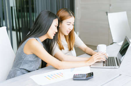 Two Asian female businesswoman working together on a laptop computer reading the screen during meeting in modern office. Business team analysis and strategy concept.