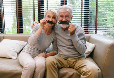 Playful elderly couple. Senior caucasian loving couple holding the fake moustache and looking at camera while relax sitting on sofa enjoy weekend at home. Happy retirement sweet moments concept.