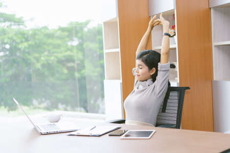 Beautiful Asian businesswoman stretching hands relaxation resting office workplace. Lifestyle woman relax after working concept. Imagens