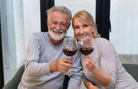 Senior romantic couple sitting together at home smiling and drinking wine and enjoy in love, looking at camera. Retired elderly joy lifestyle concept. 免版税图像