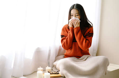 Portrait of young beautiful Asian woman sneezing and blowing nose with a tissue sitting home in the chair by the window. Young Asian woman getting sick with flu in a winter day. Woman with a cold.