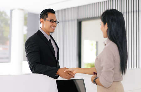 Handsome Asian businessman handshake to the receptionist the hostel reception desk. Business travel concept.