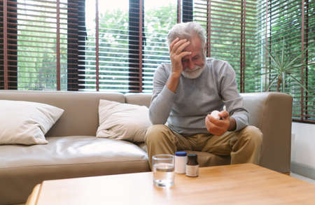 Portrait of a sick elderly man feeling sick ill suffering from headache. He taking antibiotic antidepressant painkiller pill medication to relieve pain at home. Elderly healthcare concept. Imagens
