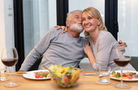Cheerful senior couple embracing in love hug and kiss eating salad and drinking red wine together with healthy food on the kitchen at home. Concept of healthy nutrition in older age and Happy retirement.