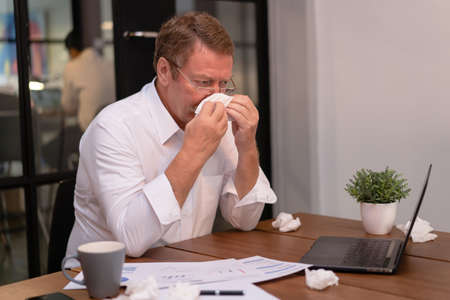 Ill at work. Senior Businessman got flu allergy sneezing blowing wiping running nose in tissue and sitting at workplace in modern office. Seasonal allergy or cold fever flu concept.