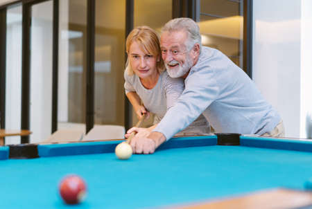Cheerful senior couple have fun in living room and husband teaching his wife for playing snooker together in home.  A new normal lifestyle and Happy retirement concept. Imagens
