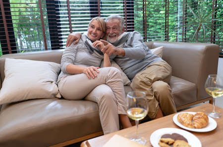 Portrait of happy old elderly caucasian couple relax sitting on the couch while embracing in love hug and talking something in living room at home. Happy retirement sweet moments.