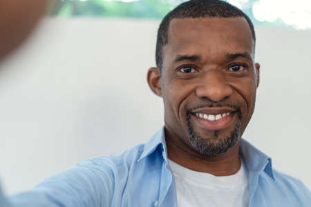Portrait of African American handsome man smiling friendly aking selfie of himself in their living room at home. People man lifestyle concept. 免版税图像