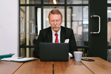 Senior financial man with glasses working on laptop computer while sitting at his desk in a bright modern office.