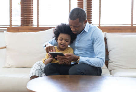 Portrait of happy African American father and son using a tablet while sofa sitting on sofa at home. Having great time together. Concept of family entertainment, education, technology.