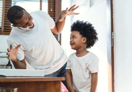 Father and son having a good time. Happy African American father with shaving foam on faces playing with his child in the bathroom.