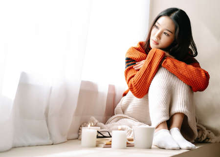 Portrait of young Asian woman wearing knitted warm sweater sitting home in the chair by the window and looking away. Copy space area, Cozy winter decorated with candles.Feeling comfortable at home. 免版税图像
