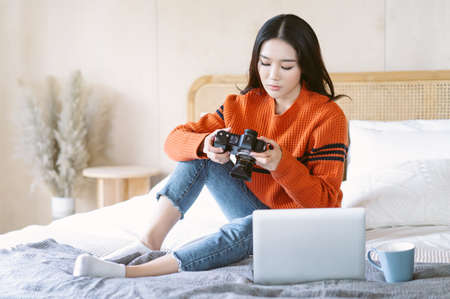 Portrait of young beautiful Asian woman in warm knitted clothes with professional camera and checking picture while sitting on bed at home.Blogger,freelance work online marketing.Small business owner. 免版税图像