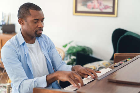 Handsome African American man plays the piano in living room at home. Creative songs concept. Leisure hobby indoors.
