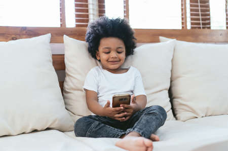 African little cute boy sitting on sofa using smartphone watching cartoons having fun enjoy on-line app for kids in living room at home. Technology new generation addicted with gadgets concept.