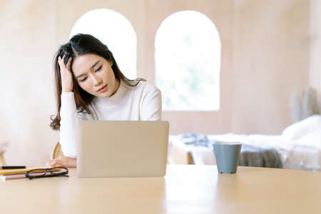 Freelance stress. Tired exhausted young beautiful Asian woman freelancer about problem with laptop, having problems with project,feeling depression,lazy during at home office desk in winter holiday. Imagens