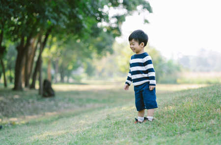 Portrait of a happy and cheerful Asian little boy standing and laughing while playing on a walk in the park. Spend time in nature forest,   Positive emotions and energy.