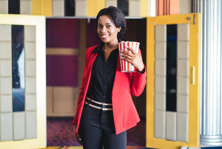 Portrait of happy african american young woman holding a popcorn  stands in front of a movie theater and looking at camera. Entertainment and enjoyment concept. Imagens