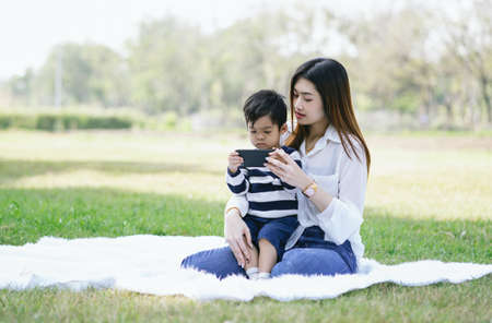 Portrait of Asian little son sit on mothers lap spend sunny day in park watching cartoon online on the phone. Spending time with modern technologies concept in holiday.