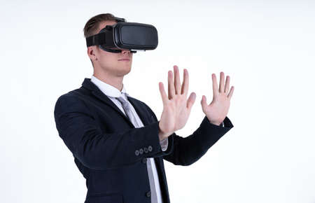 Portrait of young caucasian businessman wearing VR glasses and interacting with virtual reality isolated on white background. Technology concept