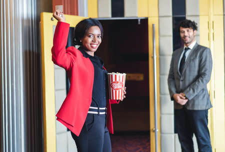 Happy african american young woman holding a popcorn and ticket stands in front of a movie theater on the background man controller worker stand front of entrance. Entertainment and enjoyment concept.